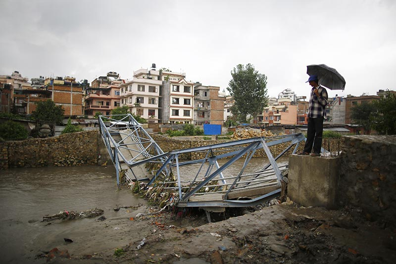 A man looking at a collapsed under-construction bridge over the Bishnumati River, in Kathmandu, on Friday, August 11, 2017. Photo: THt