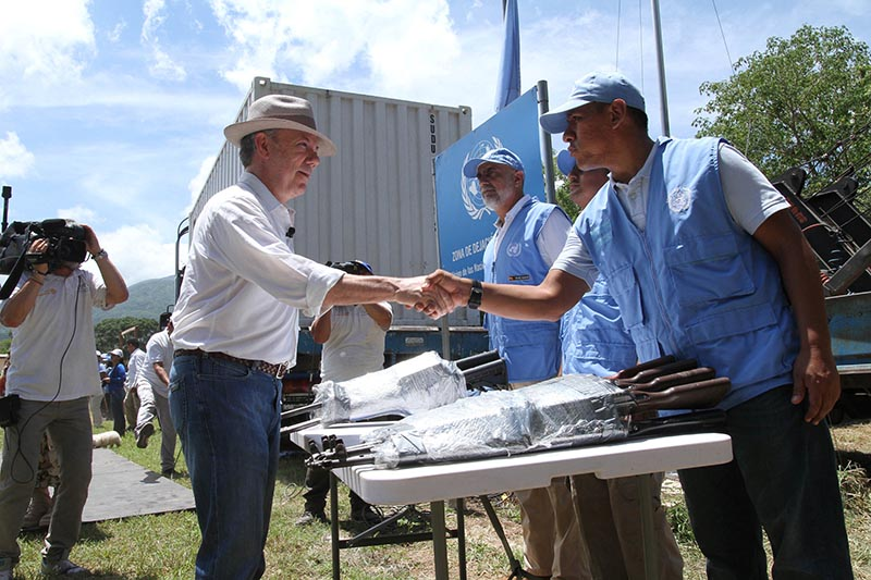 Colombia's President Juan Manuel Santos greets an observer of the UN as the last container with weapons delivered by the rebels of the FARC is turned in, in La Guajira, Colombia, on  August 15, 2017. Photo: Colombian Presidency/Handout via Reuters