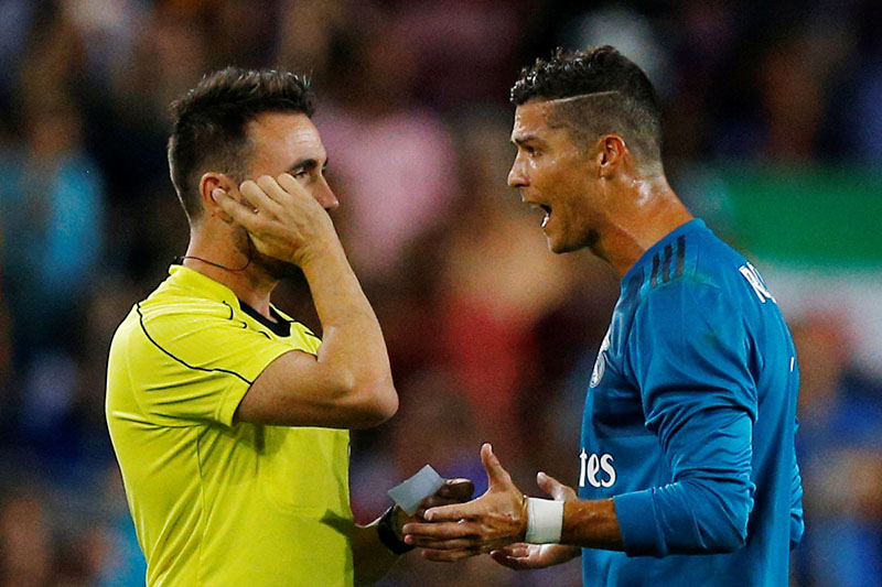 Real Madridu2019s Cristiano Ronaldo speaks with referee Ricardo de Burgos Bengoetxea after being shown a red card after receiving a second yellow card for simulation. Photo: Reuters