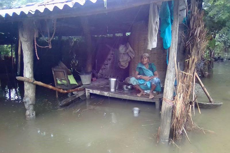 A woman sitting on a cot inside a flooded house in a Dalit settlement in Hariharpur, Nawalparasi, on Sunday, August 13, 2017. Photo: THT