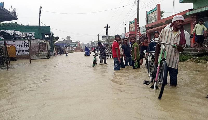 People struggling to walk through flooded roads in Birgunj Metropolis on Sunday, August 13, 2017. Photo: Ram Sarraf