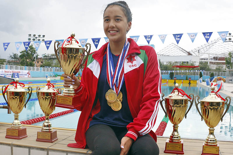 Swimming screamer Gaurika Singh pose with trophies after the 20th National Swimming Championship in Satdobato, Lalitpur, on Friday, August 18, 2017. Photo: RSS