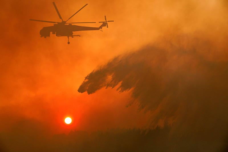 A firefighting helicopter makes water drop as a wildfire burns near the village of Metochi, north of Athens, Greece, on August 15, 2017. Photo: Reuters