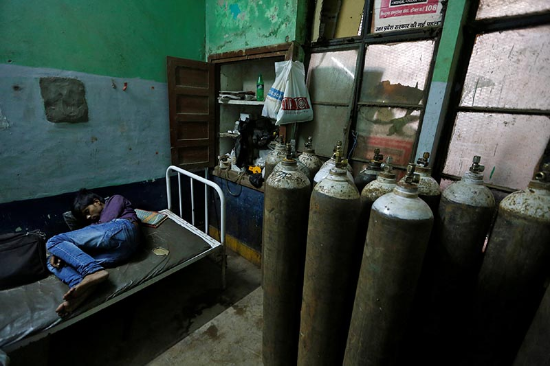 A man sleeps in a room containing oxygen tanks in the Baba Raghav Das hospital in Gorakhpur district, India, on August 13, 2017. Photo: Reuters