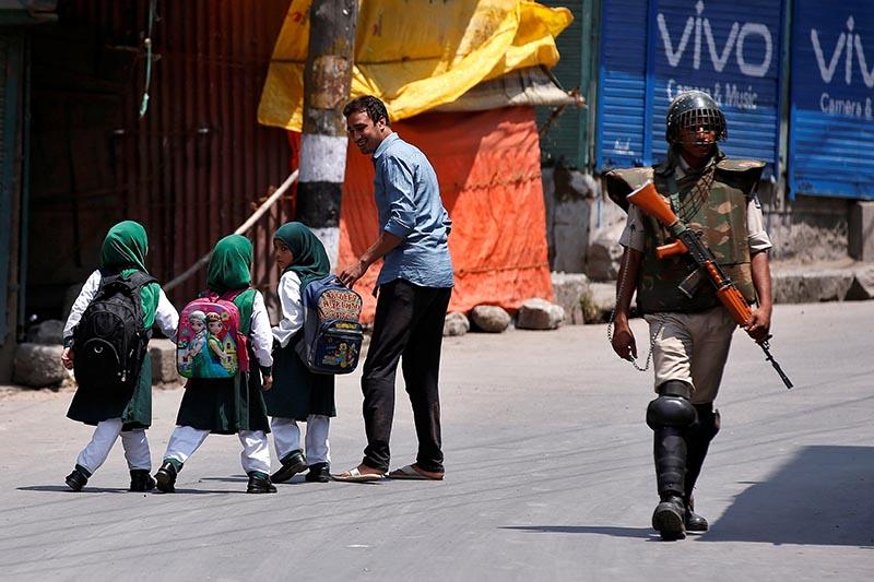 School children walk past an Indian policeman during a curfew in downtown Srinagar, on July 28, 2017. Photo: Reuters