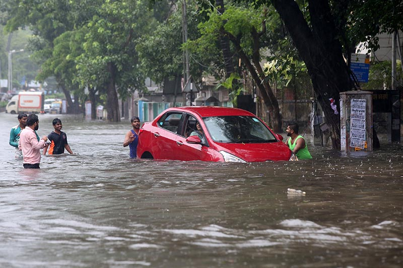 People help a woman to move her car through a water-logged road during rains in Mumbai, India, on August 29, 2017. Photo: Reuters