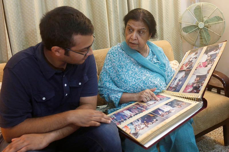 Rehana Khursheed Hashmi, 75, migrated from India with her family in 1960 and whose relatives, live in India, speaks with her grandson Zain Hashmi, 19 while looking family photo album at her residence in Karachi, Pakistan, on August 7, 2017. PHoto: Reuters