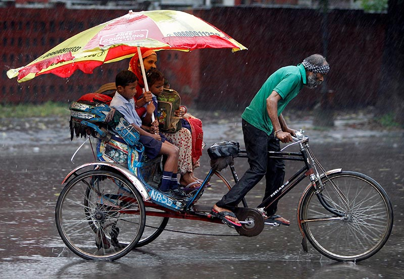 A woman and her children ride in a rickshaw during heavy rains in Chandigarh, India, on August 21, 2017. Photo: Reuters.