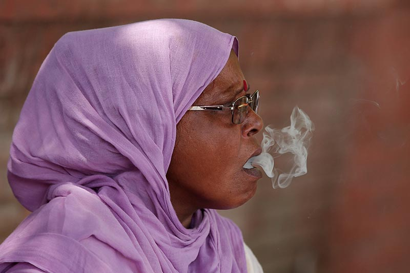 A woman smokes a beedi or local cigarette hand-rolled with tobacco leaf on a roadside in New Delhi, India, on May 24, 2017. Photo: Reuters