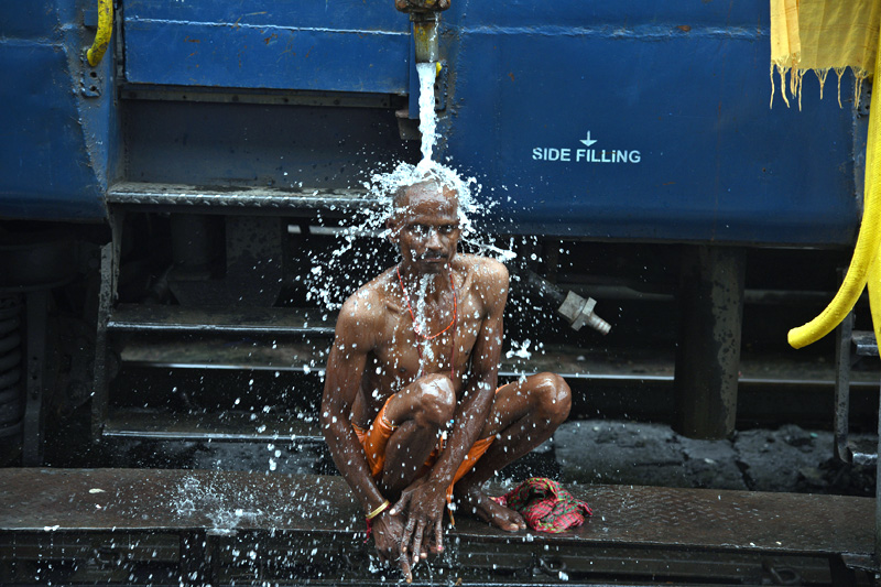 A man bathes using a pipe that supplies water to trains at a railway station in Guwahati, India, August 12, 2017. Photo: Reuters