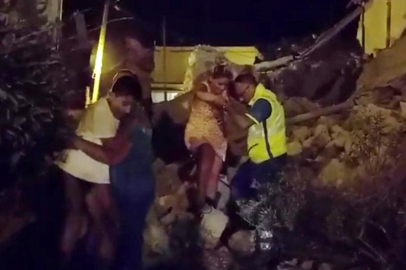 A woman is helped out of debris and rubble after an earthquake hit the island of Ischia, off the coast of Naples, Italy, on August 21, 2017 in this still image taken from video. Photo: Reuters/Vincenzo Precisano