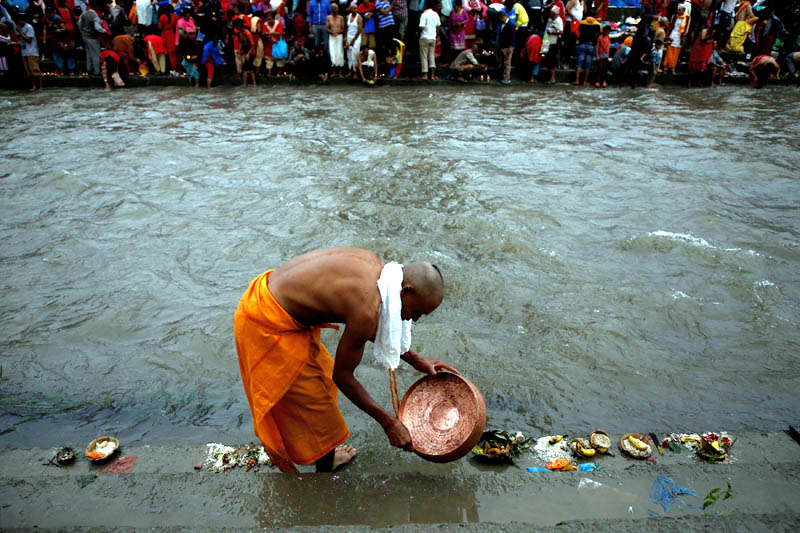 A devotee washes his dish after performing ritual on the Bagmati River during Kuse Aunshi (Father's Day) at Gokarna Temple in Kathmandu, on August 21, 2017. Photo: Reuters