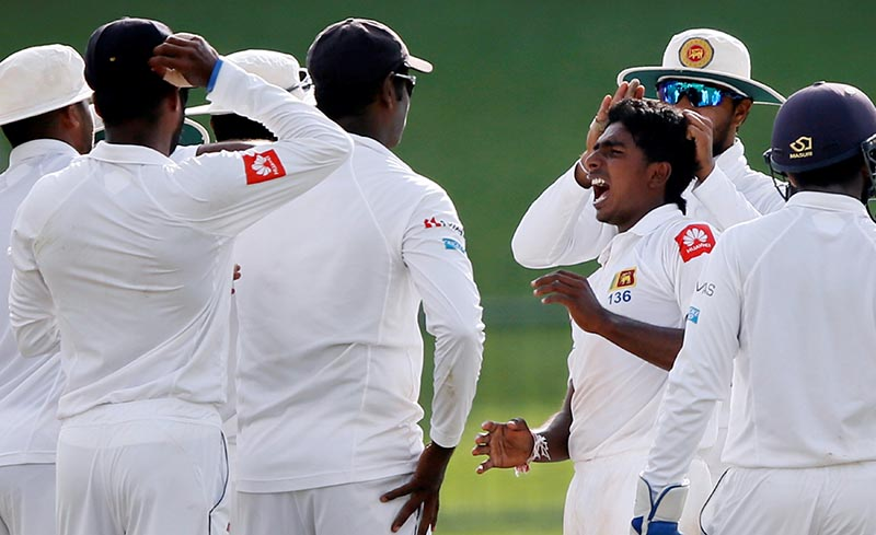 Sri Lanka's Lakshan Sandakan celebrates with captain Dinesh Chandimal and teammates. Photo: Reuters