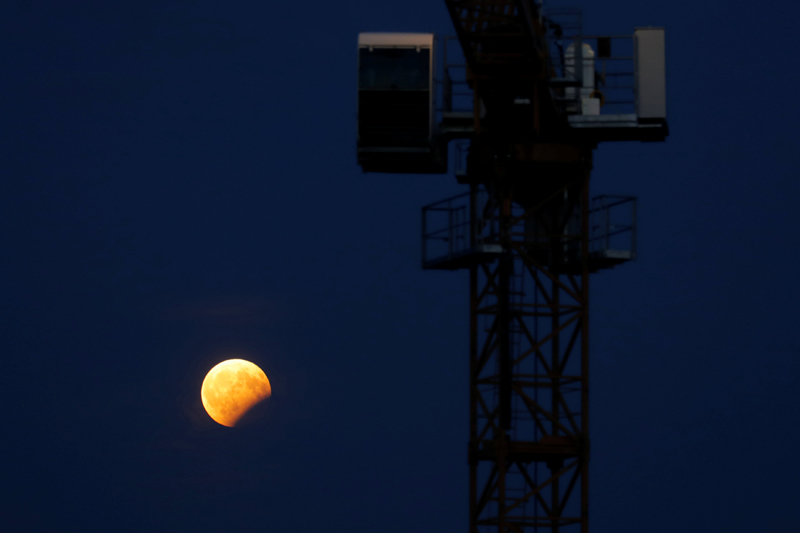 The moon rises with the earth casting a shadow on it behind a construction crane during a partial lunar eclipse in Vienna, Austria, August 7, 2017. Photo: Reuters