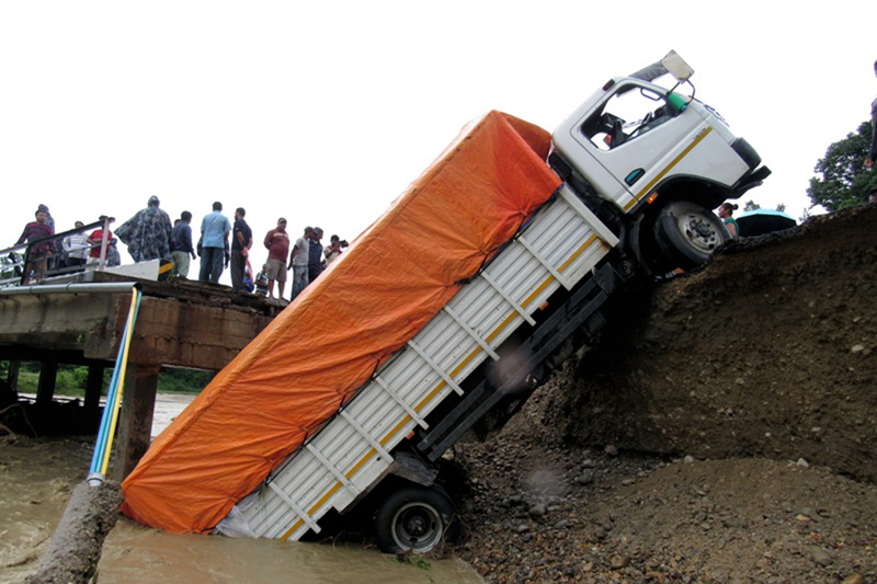 A goods-laden truck plunges off the Janga River bridge, along the East-West Highway, as the bridge was completely damaged in flash flood, in Mahottari, on Sunday, August 13, 2017. Photo: RSS