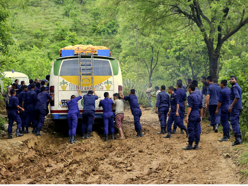 Police personnel push a bus stuck in a muddy road along the Khadbari-Dhankuta road stretch in Sankhasubaha district, on Wednesday, August 30, 2017. Photo: RSS