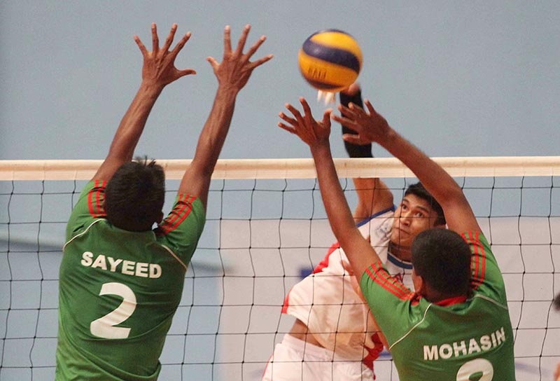 Nepalu2019s Man Bahadur Shrestha attempts a spike against Bangladeshi players during their friendly volleyball match at the Nepal Army Sports Complex in Lalitpur on Wednesday, August 30, 2017. Photo: Udipt Singh Chhetry/THT
