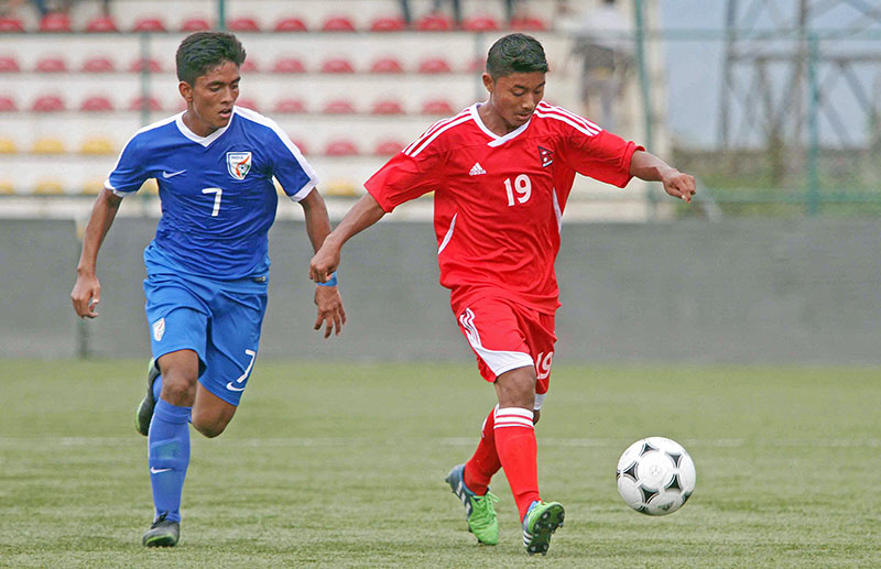 Nepali players Shishir Lekhi (red jersey) dribbles ball against Ravi Bahadur Rana of India during the SAFF U-15 Championship at the ANFA Complex grounds in Lalitpur on Wednesday. Photo: Udipt Singh Chhetry