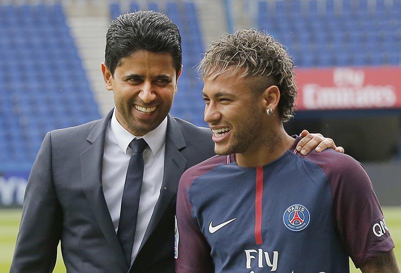 Brazilian soccer star Neymar walks away with the chairman of Paris Saint-Germain Nasser Al-Khelaifi (left) following a press conference in Paris, on Friday, Aug. 4, 2017. Photo: AP