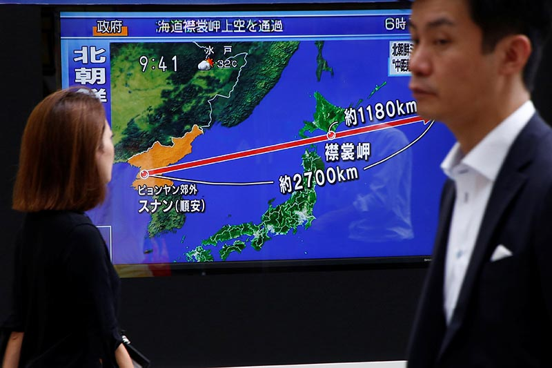 Pedestrians walk past a TV set showing news about North Korea's missile launch in Tokyo, Japan, on August 29, 2017. Photo: Reuters