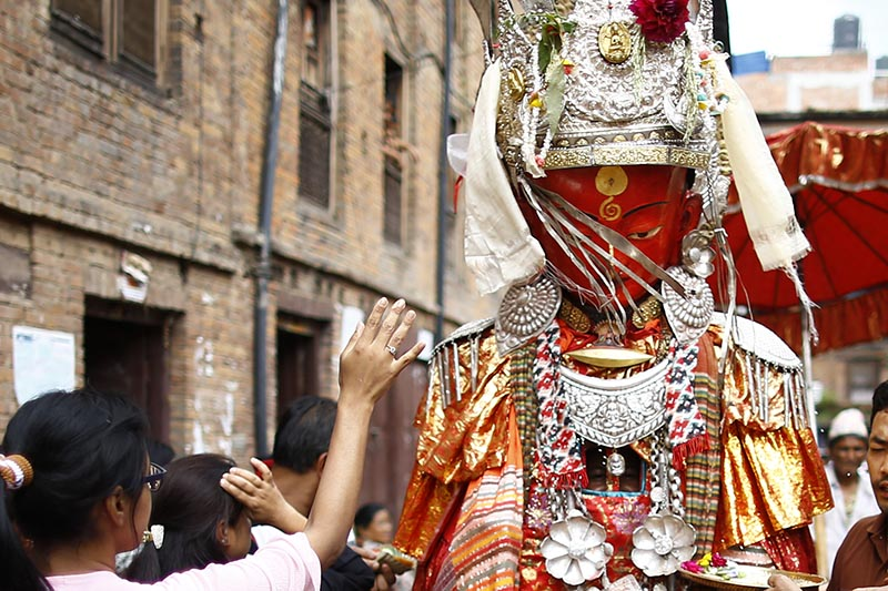 Devotees offer prayers to a person concealed inside the idol of Deity Dipankar Buddha parading around the ancient city to receive prayers offered by devotees during Pancha Dan festival in Bhaktapur, Nepal on Saturday, August 19, 2017. The major highlights of the festival are giving away five elements also known as five summer gifts including wheat grains, rice grains, salt, money and fruit for prayers, wishing good health and prosperity. The Buddhists observe Pancha Dan by displacing gigantic antique statues of Deity Dipankar Buddha and devotees worshipping them across the city. Photo: Skanda Gautam