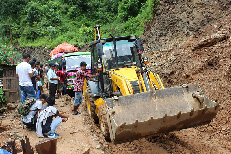 An excavator is being used to pull a passenger bus stuck in muddy road along Bhaluswara-Barpak road stretch in Gorkha district, on Wednesday, August 30, 2017. Photo: RSS