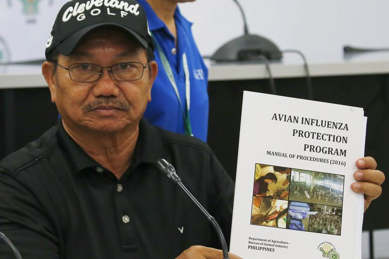 Department of Agriculture Secretary Emmanuel Pinol holds a manual for Avian Influenza Protection during a news conference on the confirmation of the first bird flu case in the country, in Manila, Philippines, on Friday, August 11, 2017. Photo: AP