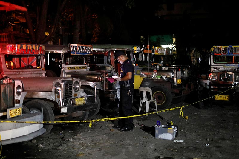 A member of Philippine National Police Scene of the Crime operative examines a crime scene, where police said, a man was killed during anti-drug operations by the police in Caloocan city, Metro Manila, Philippines, on August 17, 2017. Photo: Reuters