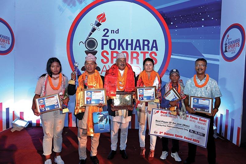(From left) Mamata Dagaura, Sun Bahadur Lama, Khadga Ranabhat, Aruna Shahi, Durga Adhikari, father of Kumar Adhikari, and Binod Kayastha hold the trophies after the second Pokhara Sports Award in Pokhara, on Saturday. Photo: THT