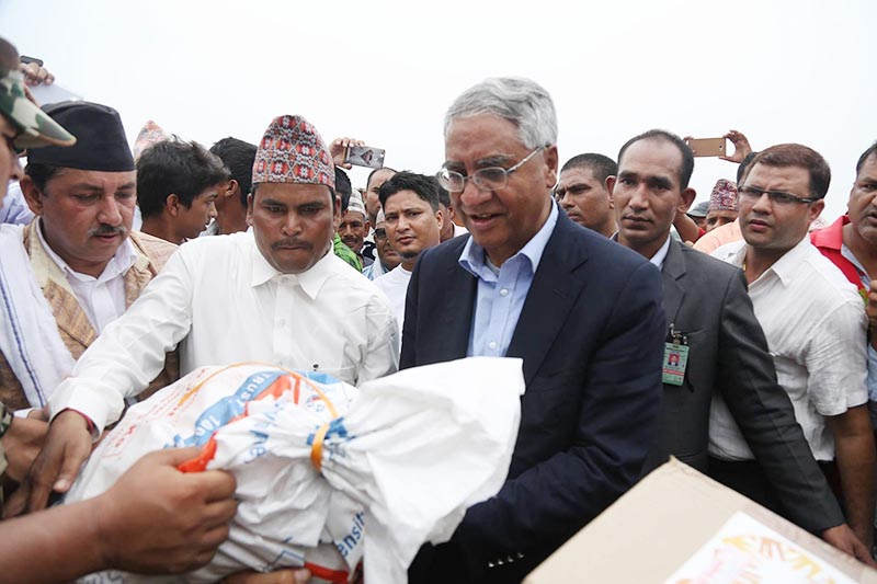 Prime Minister Sher Bahadur Deuba distributes relief package to the flood survivors and bereaved families in Rapti-Sonari Rural Municipality of Banke district, on Thursday, August 17, 2017. Photo: RSS