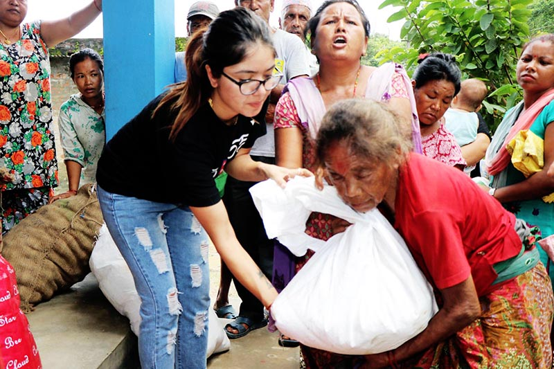 Nepali cine artist Puja Sharma handing over reilief items to flood victim in Chitwan district, on Thursday, August 17, 2017. Courtesy: Gyanendra Tamang