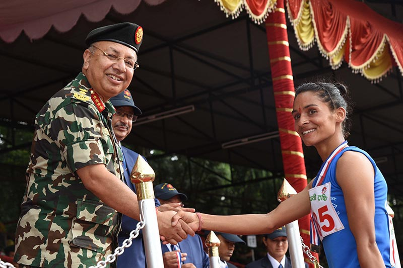 Chief of the Army Staff Gen Rajendra Chhetri shakes hands with athlete Saraswoti Bhattarai after the 1,500m race of the CoAS Trophy in Lalitpur on Friday, August 18, 2017. Photo: THT