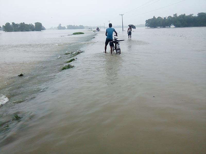 People walking through waterlogged road along the Gaur-Chandrapur road section, in Matsari in Rautahat district on Saturday, August 12, 2017. The incessant rainfall has swollen Jhanjhekhola. Photo: Prabhat Kumar Jha/THT