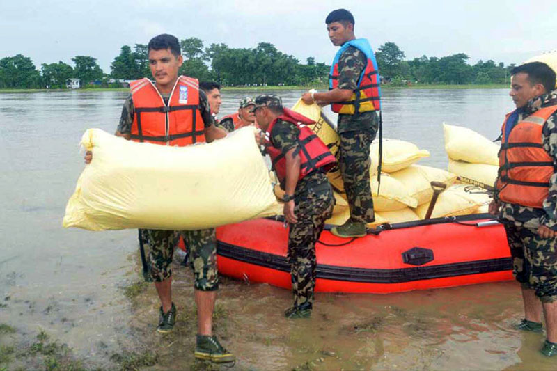 Army personnel unload relief package for flood victims in Jhapa district, on Monday, August 14, 2017. Photo: RSS