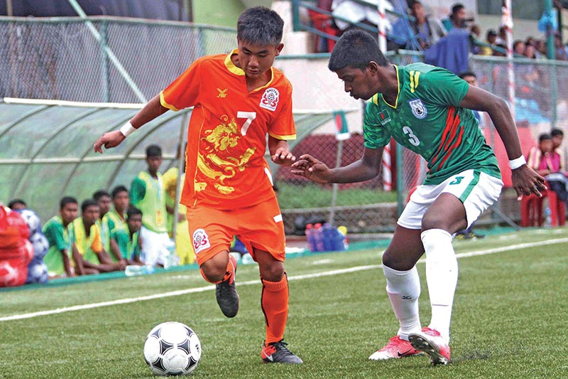 Dorji Khando (left) of Bhutan and Yeasin Arafat vie for the ball during their SAFF U-15 Championship match at the ANFA Complex  grounds in Lalitpur, on Tuesday. Photo: THT