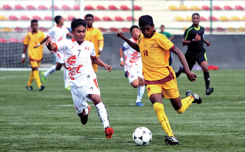 Dorji Khando of Bhutan (left) vies for the ball with Rumes Mendis of Sri Lanka during their SAFF U-15 nChampionship match at the ANFA Complex grounds in Lalitpur on Sunday. Bhutan won the match 6-0. Photo: THT