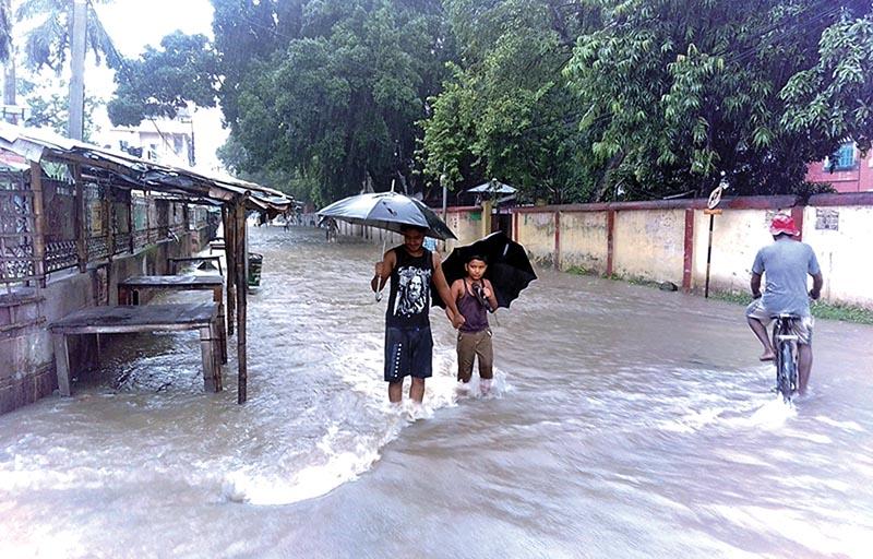 People wading through a waterlogged street in Rajbiraj Municipality, Saptari district, on Saturday. Photo: THT