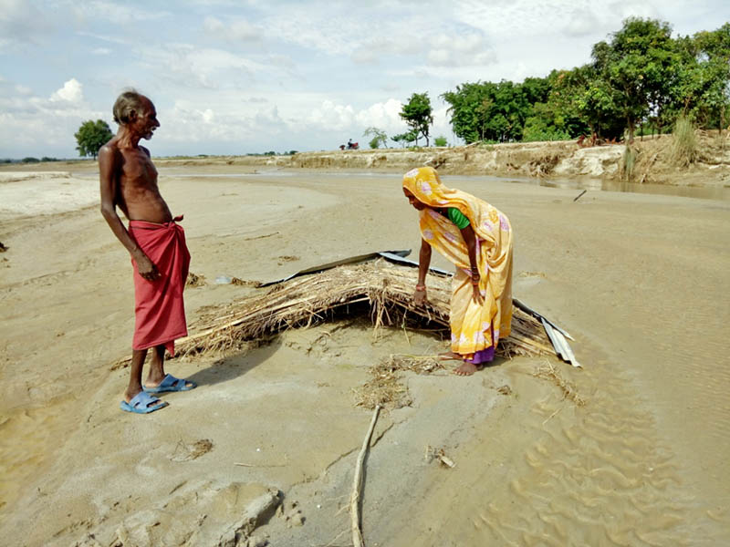A man looks on as his wife pulls a makeshift hut roof in Saptari district, on Sunday, August 20, 2017. Photo: Byas Shankar Upadhayay