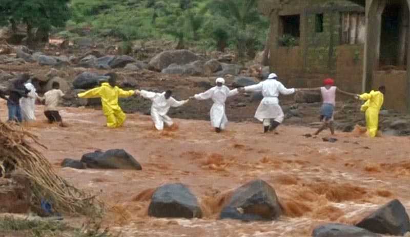 People wearing protective suits hold hands as they cross a river after a mudslide in the mountain town of Regent, Sierra Leone, on August 15, 2017 in this still image taken from a video. Photo: Reuters TV