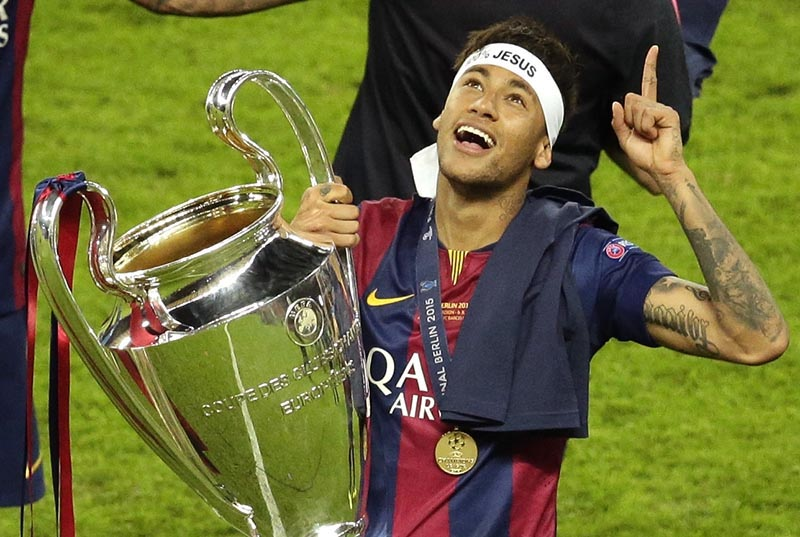 File - Barcelona's Neymar celebrates with the trophy after the Champions League final soccer match between Juventus Turin and FC Barcelona at the Olympic stadium in Berlin, on  Saturday, June 6, 2015. Photo: AP