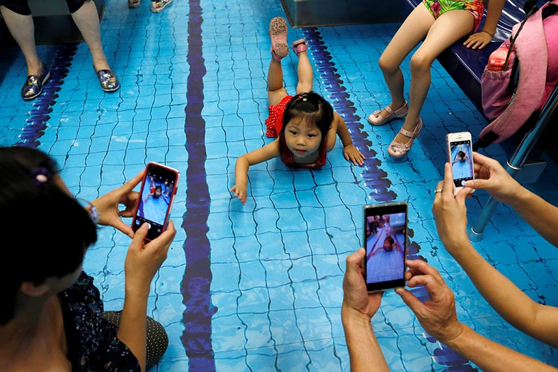 People take photo as a child poses at a sports-themed Mass Rapid Transit (MRT) train ahead of Summer Universiade, in Taipei, Taiwan, on August 1, 2017. Photo: Reuters