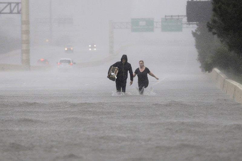 Two people walk down a flooded section of Interstate 610 in floodwaters from Tropical Storm Harvey,  in Houston, Texas, on Sunday, August 27, 2017.