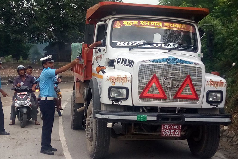 FILE PHOTO: Traffic Police Officer inspets documents of a tipper truck in Tanahun district, on Monday, August 28, 2017. Photo: RSS