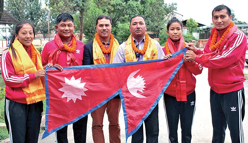 Nepalu2019s judo players and officials hold the national flag after the farewell programme in Kathmandu, on Thursday. Photo: THT