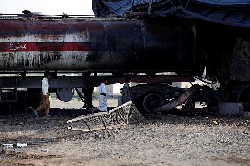 Boys walks by a fuel tanker truck destroyed by a Saudi-led air strike on a nearby checkpoint of the armed Houthi movement near Sanaa, Yemen, on August 30, 2017. Photo: Reuters