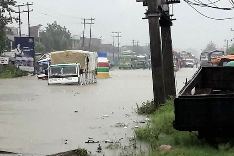 Trucks are seen half submerged while parked alongside a road, along the East-West Highway, in Bara, on Saturday, August 12, 2017. Photo: Pushpa Raj Khatiwada
