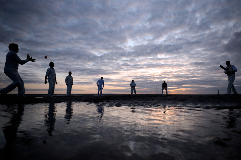 Players warm up ahead of the annual Brambles sandbank cricket match at low tide in the Solent, Britain, August 24, 2017. Photo: Reuters