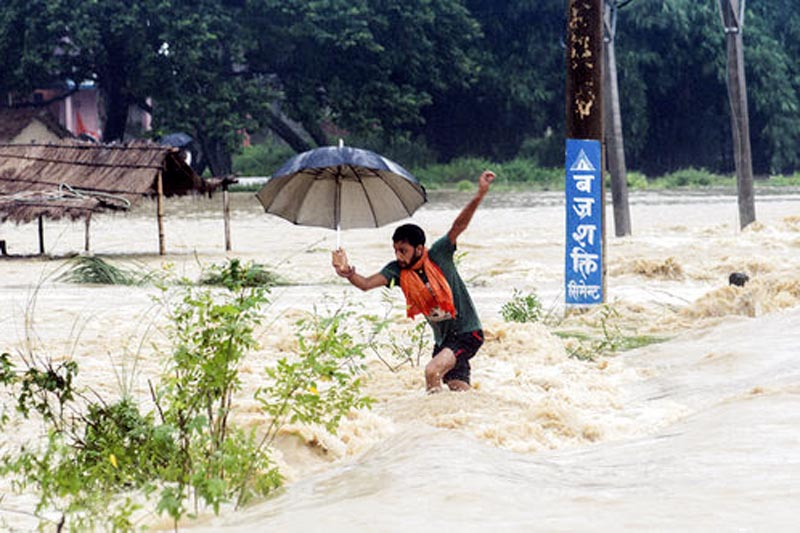 A Nepali man looses his balance while crossing a flooded street in Birgunj, Sunday, August 13, 2017. Photo: AP