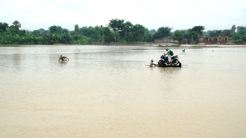 A man pulls a motorbike and its rider along the inundated area in Rautahat district, on Monday, August 14, 2017. Photo: Prabhat Kumar Jha
