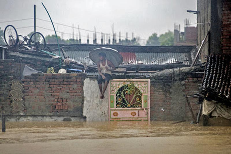 A Nepaliman sits on the wall of his house in a partially submerged village in Birgunj, Nepal, Sunday, August 13, 2017. Photo: AP
